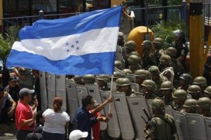 Supporters of ousted Honduras' President Manuel Zelaya protest outside the entrance to the international airport in Tegucigalpa, Sunday, July 5, 2009. After the Organization of American States, OAS, suspended Saturday night Honduras' participation in the organization because of last week coup, Zelaya took off for home Sunday in a Venezuelan jet in a high-stakes attempt to return to power, even as the interim government told its military to turn away the plane. (AP Photo/Dario Lopez-Mills)