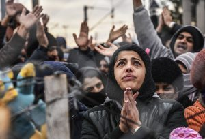Migrants protest behind a fence against restrictions limiting passage at the Greek-Macedonian border, near Gevgelija, on December 1, 2015. Since last week, Macedonia has restricted passage to northern Europe to only Syrians, Iraqis and Afghans who are considered war refugees. All other nationalities are deemed economic migrants and told to turn back. Macedonia on November 29 finished building a fence on its frontier with Greece becoming the latest country in Europe to build a border barrier aimed at checking the flow of migrants. / AFP / ARMEND NIMANI (Photo credit should read ARMEND NIMANI/AFP/Getty Images)